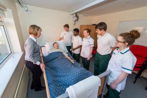 Five student nurses 和 a lecturer at the bedside of a synthetic patient