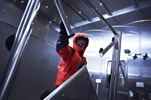 man in a red protective suit inside a laboratory filled with angled metal posts
