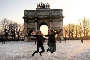 two girls jumping in front of the champs elysees structure