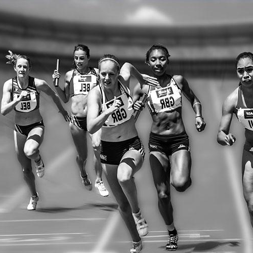 A group of female athletes are running on a racetrack