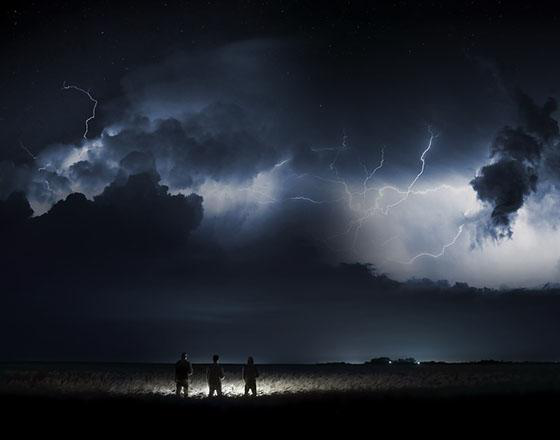 Three people st和 silhouetted in a field at night as lightening strikes the sky