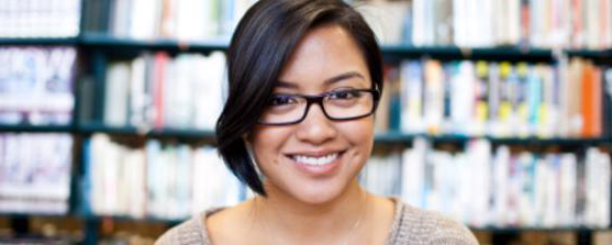 A smiling student with glasses in a library