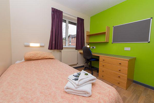 A bedroom inside University of Worcester accommodation. There is a single bed, a large pin board, desk, chest of drawers 和 a window in the room.