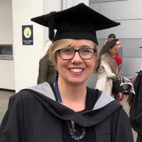 woman with glasses in graduation robes