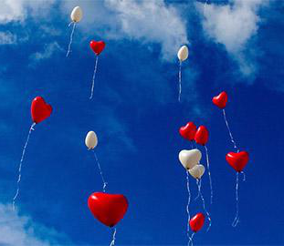red 和 white heart-shaped balloons in a blue sky