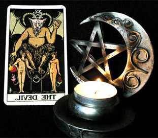 tarot card of the devil beside a star a moon and a c和le